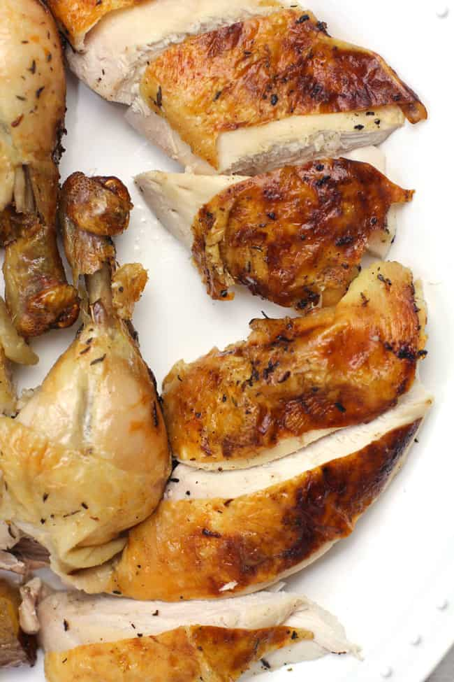 Overhead shot of sliced roasted chicken on a white platter.
