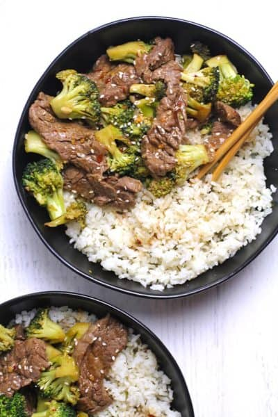 Overhead shot of two black bowls of beef and broccoli stir fry, over rice with chop sticks.