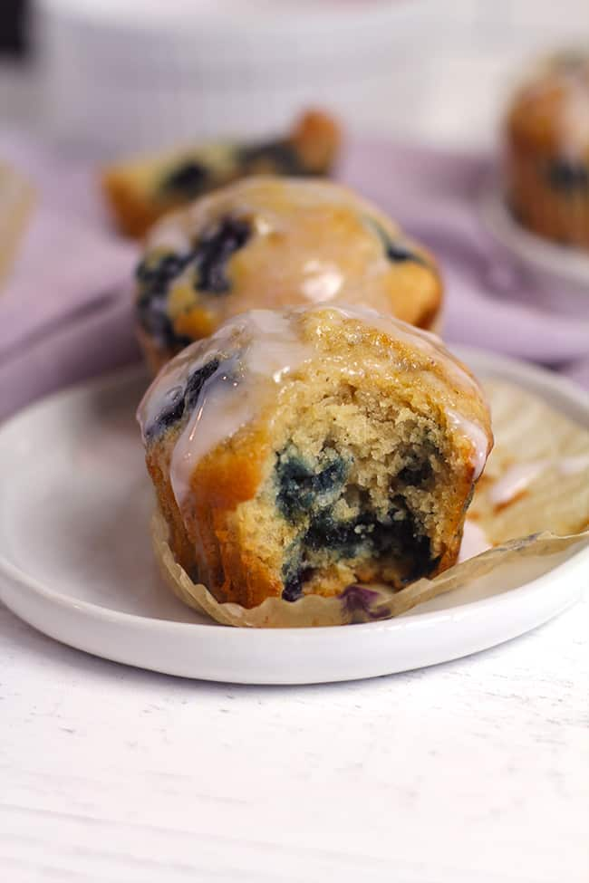 Side shot of a plate of blueberry muffins with a yogurt glaze, and a big bite out of the one in view.