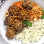 Overhead shot of a gray and white bowl of curried meatballs and rice, on a white background.