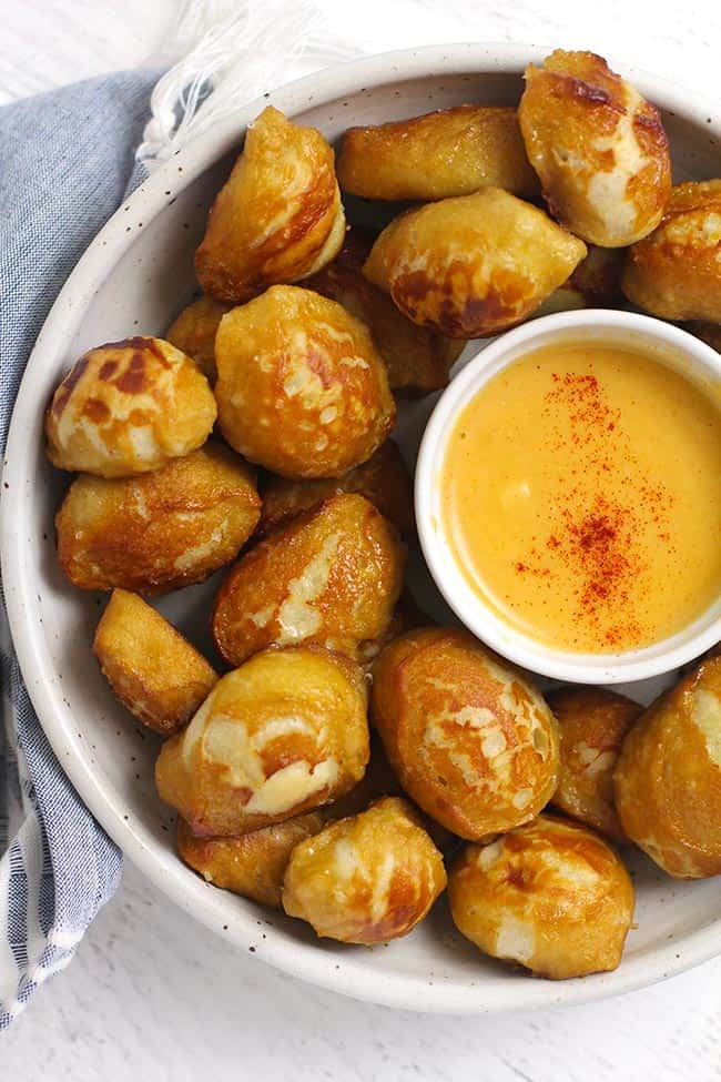 Overhead shot of a white bowl of pretzel bites, with a small bowl of cheese dip.