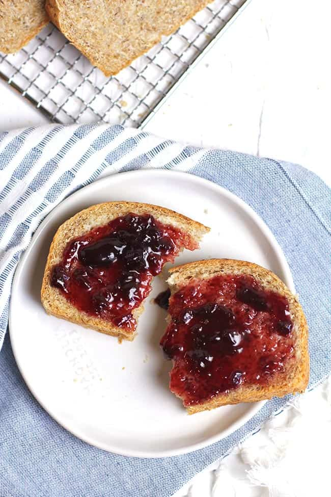 Overhead shot of a small plate with a piece of fresh bread with butter and jam, on a blue and white napkin.
