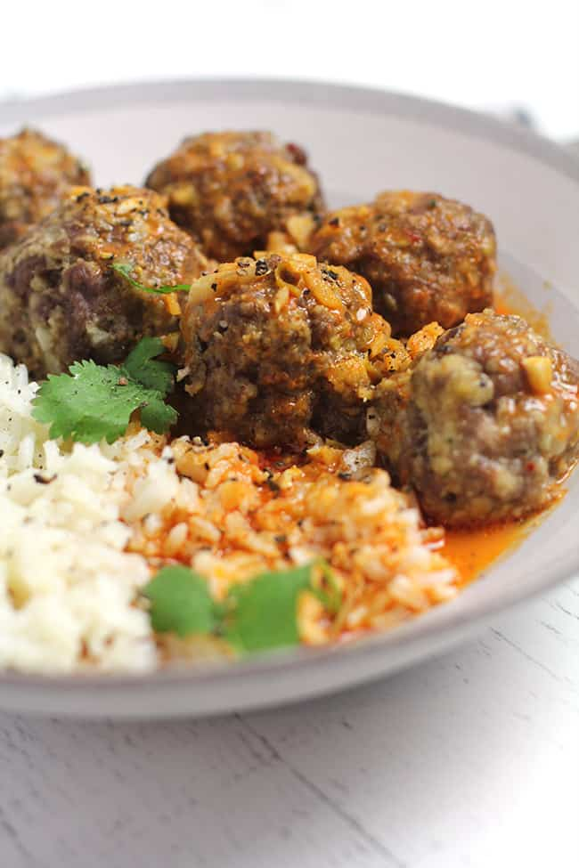 Side shot of a bowl of curried meatballs and rice.