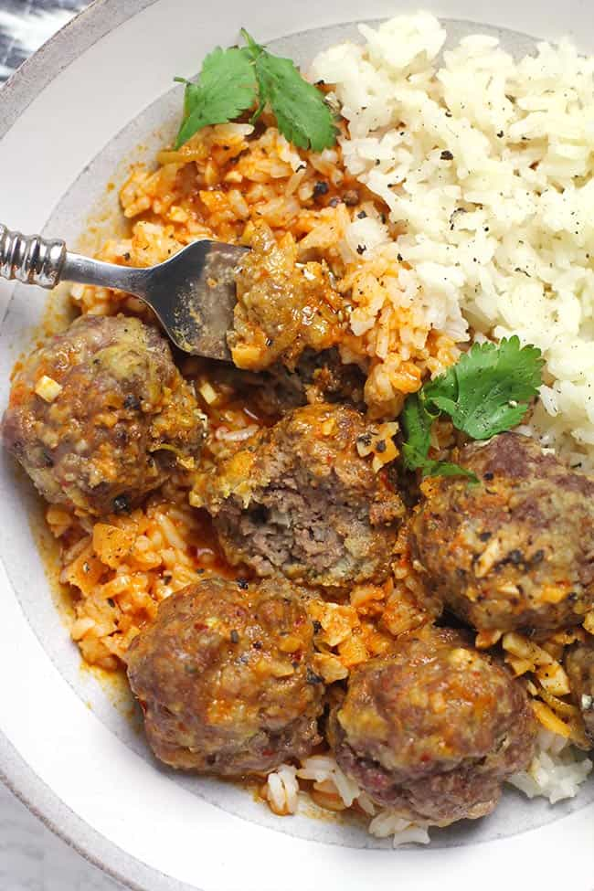 Closeup shot of a bowl of curried meatballs and rice, with a forkful of meatball.