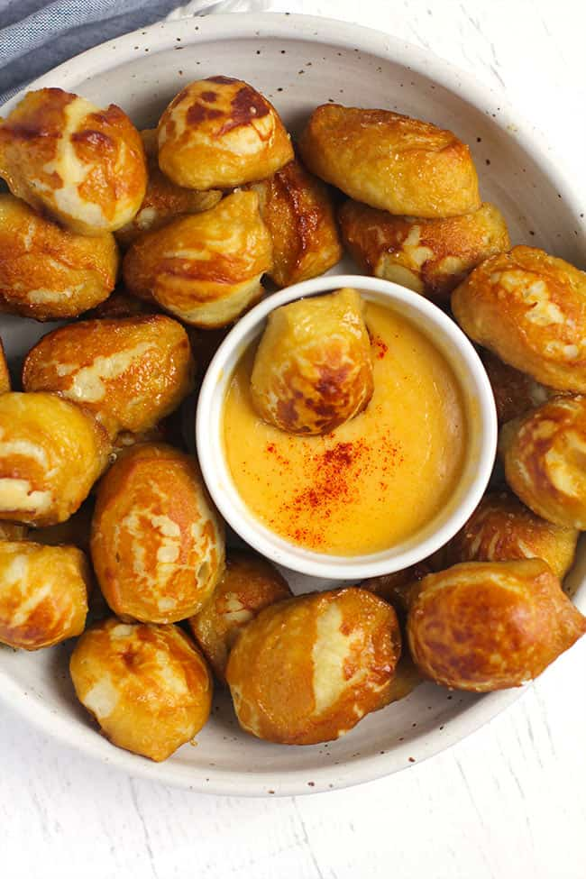 Overhead shot of a white bowl of homemade pretzel bites, with a small bowl of cheese dip in the middle holding one pretzel bite.