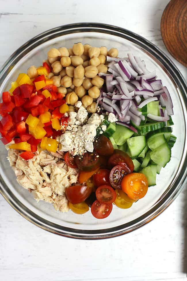Overhead shot of a glass bowl of chickpea tuna salad, divided by ingredient type.