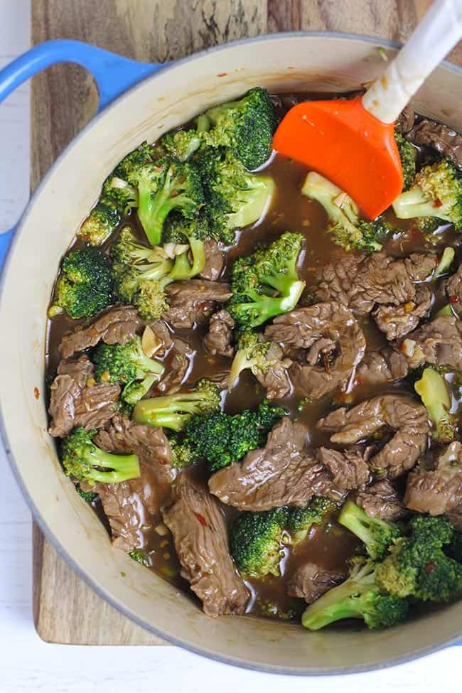 Overhead shot of a blue dutch oven of beef and broccoli stir fry, with an orange spatula.