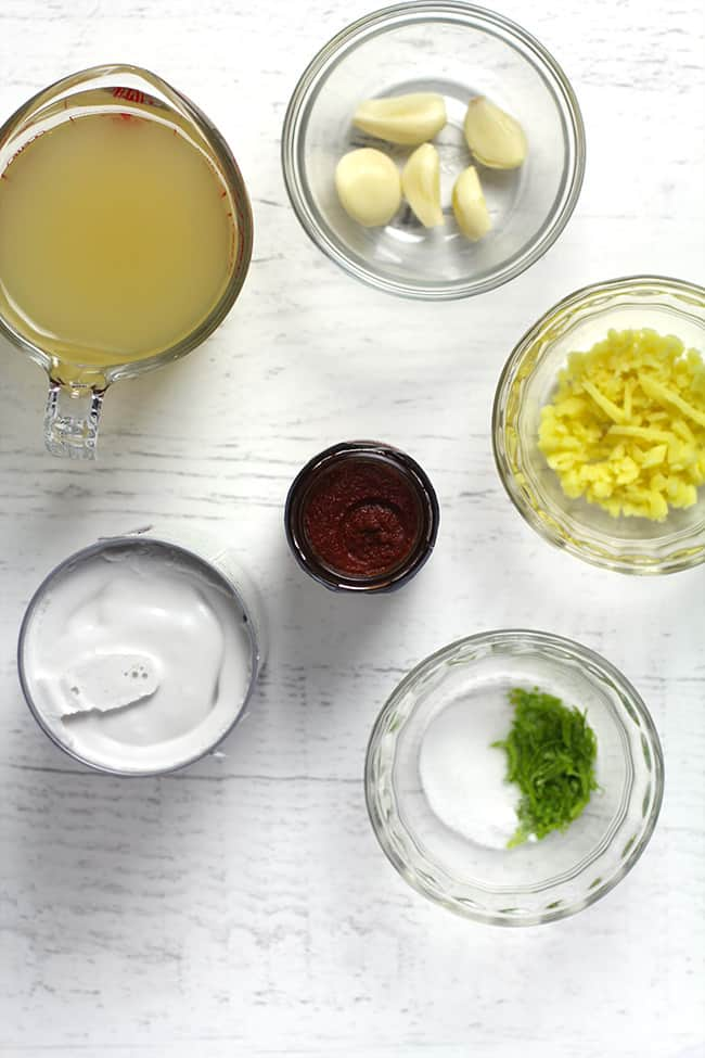 Overhead shot of curry sauce ingredients, on a white background.
