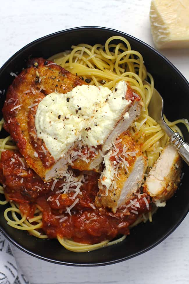 Overhead shot of a black bowl with a serving of Chicken Parm on a bed of spaghetti with marinara sauce.