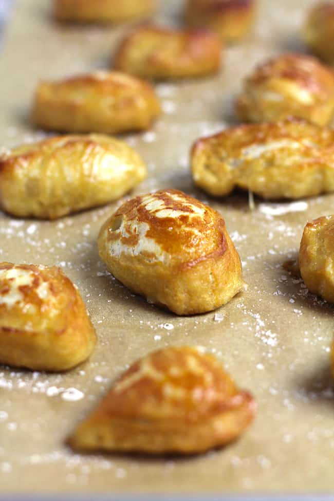 Side shot of a sheet pan of just baked homemade pretzel bites.