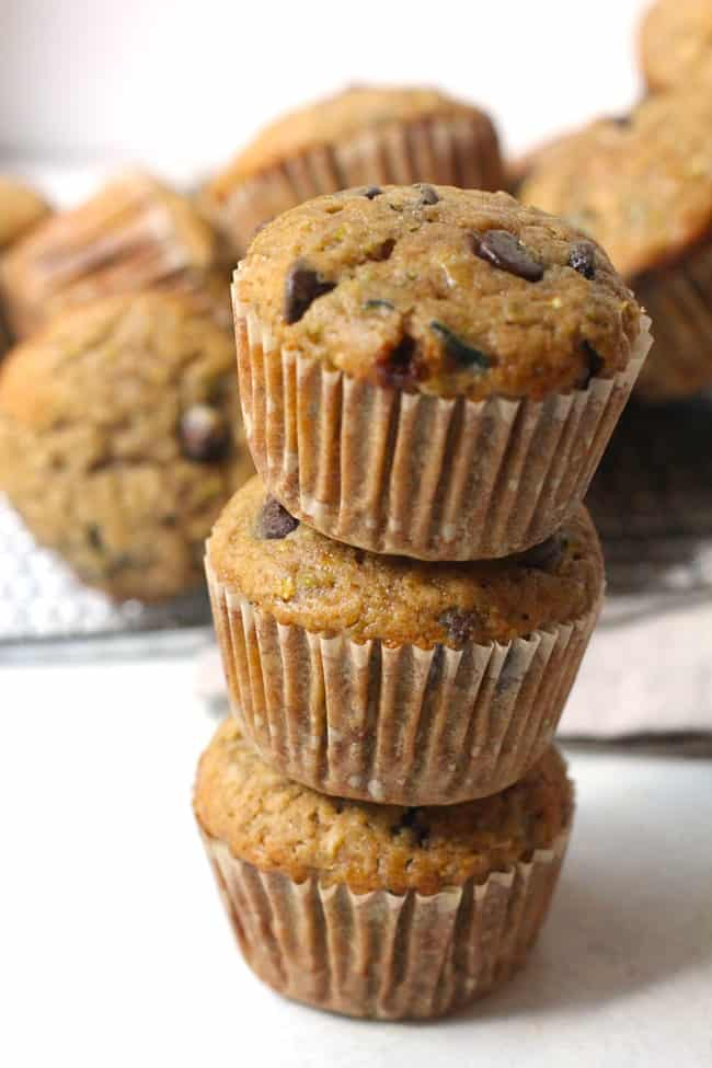 Side shot of a stack of three chocolate chip zucchini muffins, with other muffins in the background.