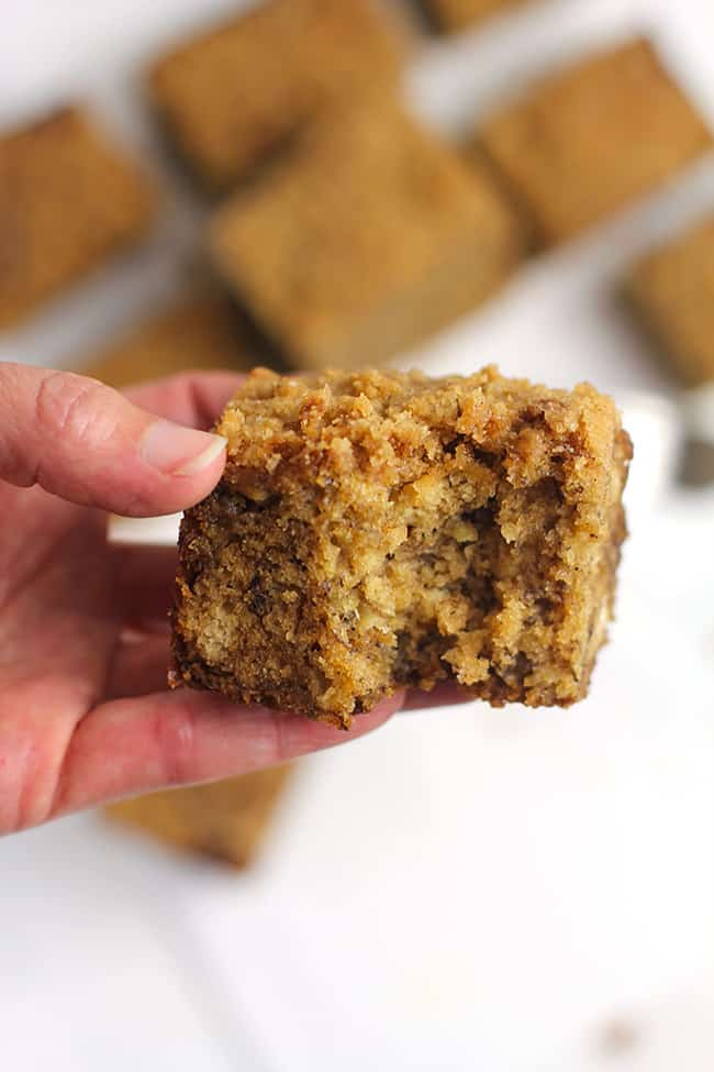 My hand holding a piece of banana coffee cake, with a bite out.