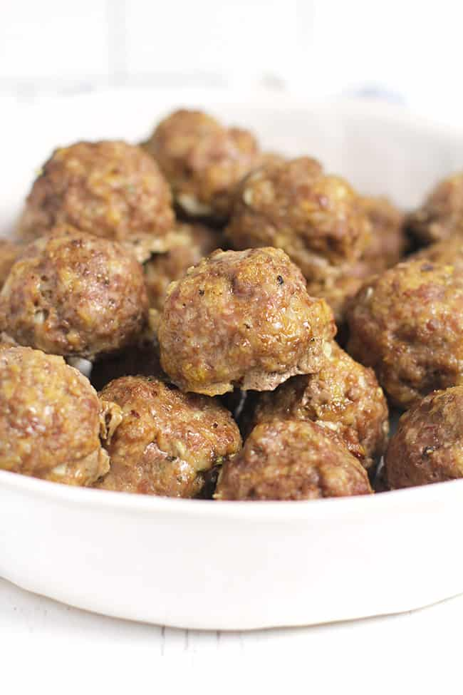 Side shot of a white dish of baked Italian meatballs.