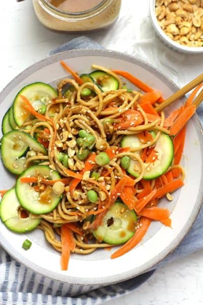 Overhead shot of a bowl of sesame noodles with vegetables and peanuts.