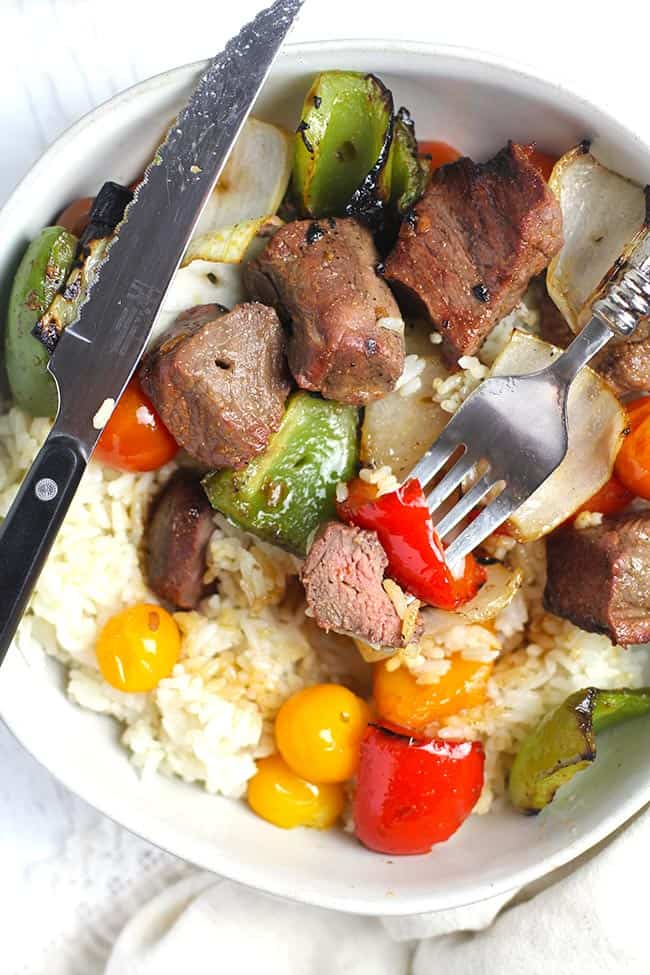 Overhead shot of a bowl of steak kabobs and veggies, over rice.