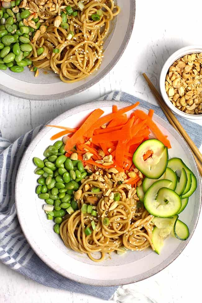 Overhead shot of two bowls of peanut sesame noodles with vegetables, on a white background.