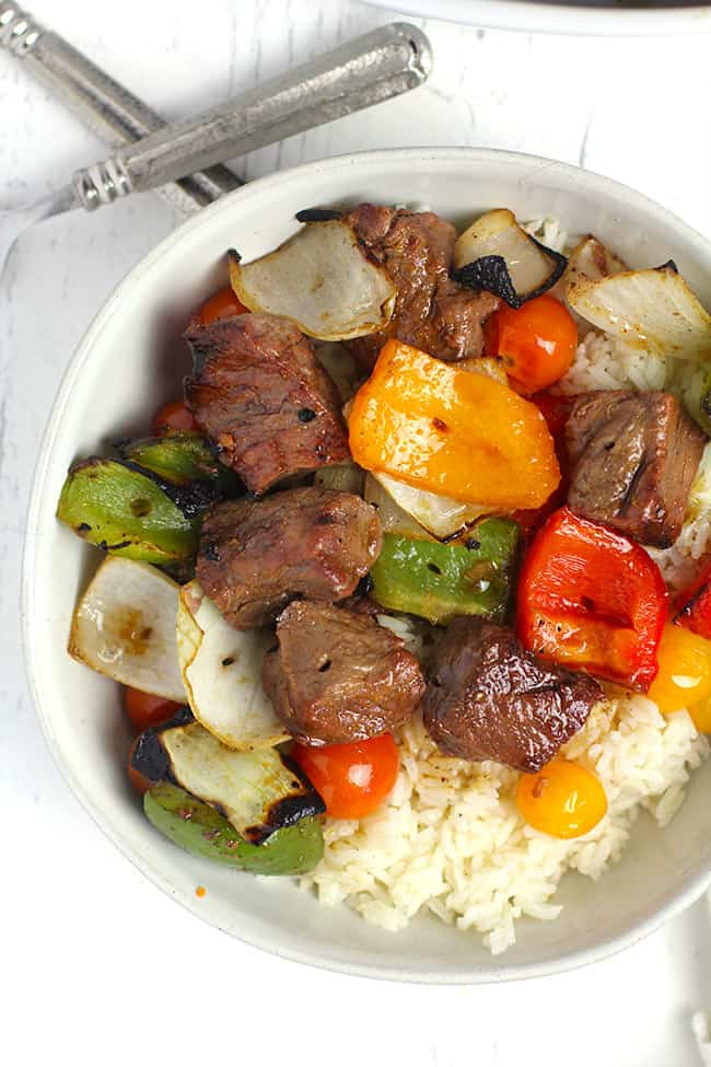 Overhead shot of a white bowl of steak kabobs, bell peppers, and onions, over rice.