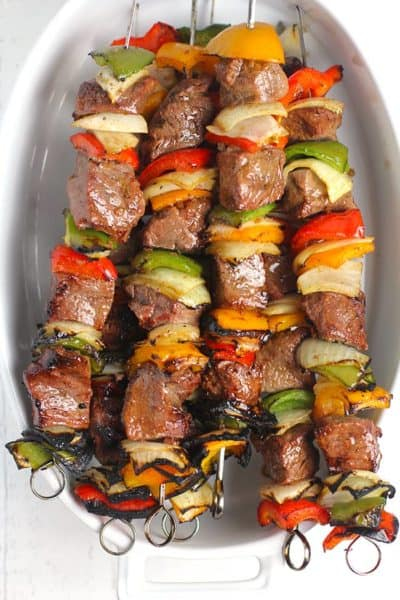 Overhead shot of an oblong white dish, with a bunch of grilled steak kabobs inside.