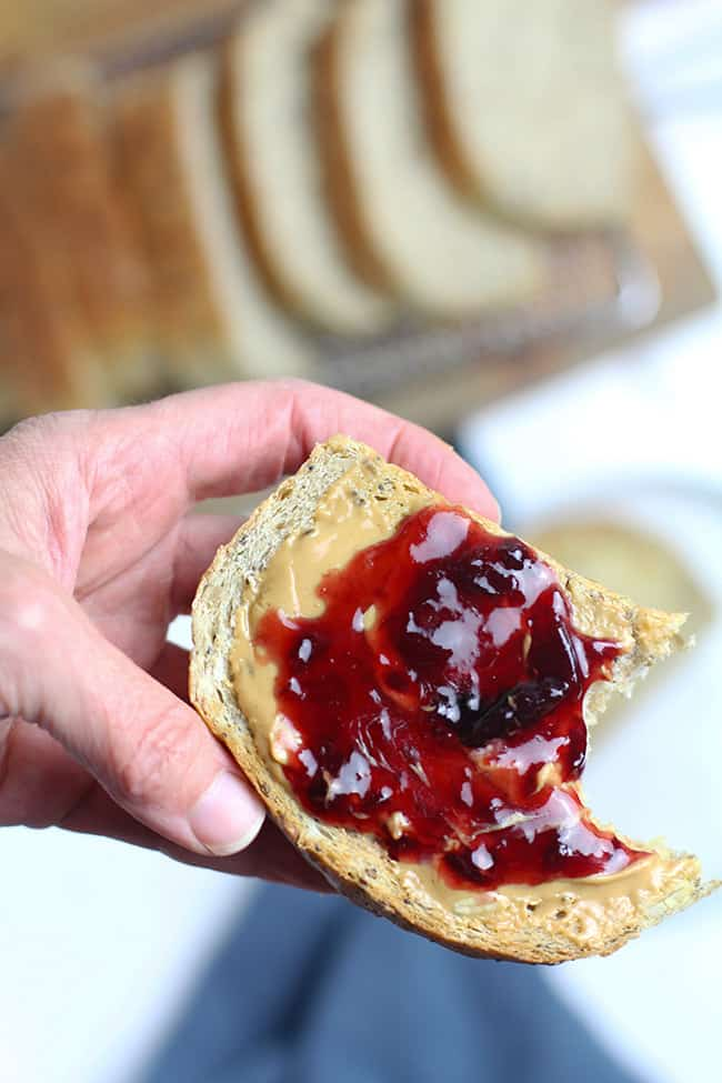 My hand holding a slice of multi-grain seeded bread, with peanut butter and jelly on top.
