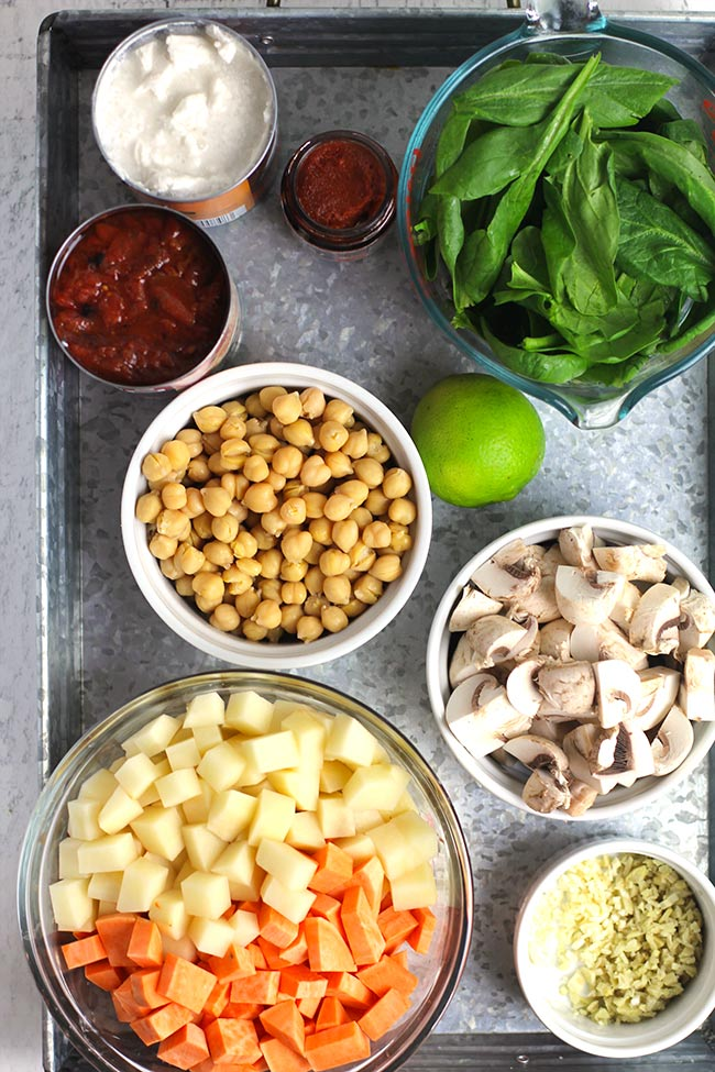 Overhead shot of a gray tray of ingredients for the coconut curry vegetable soup.
