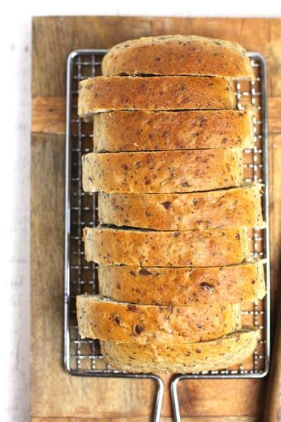 Overhead shot of a loaf of sliced multi-grain seeded bread, on a wooden cutting board.