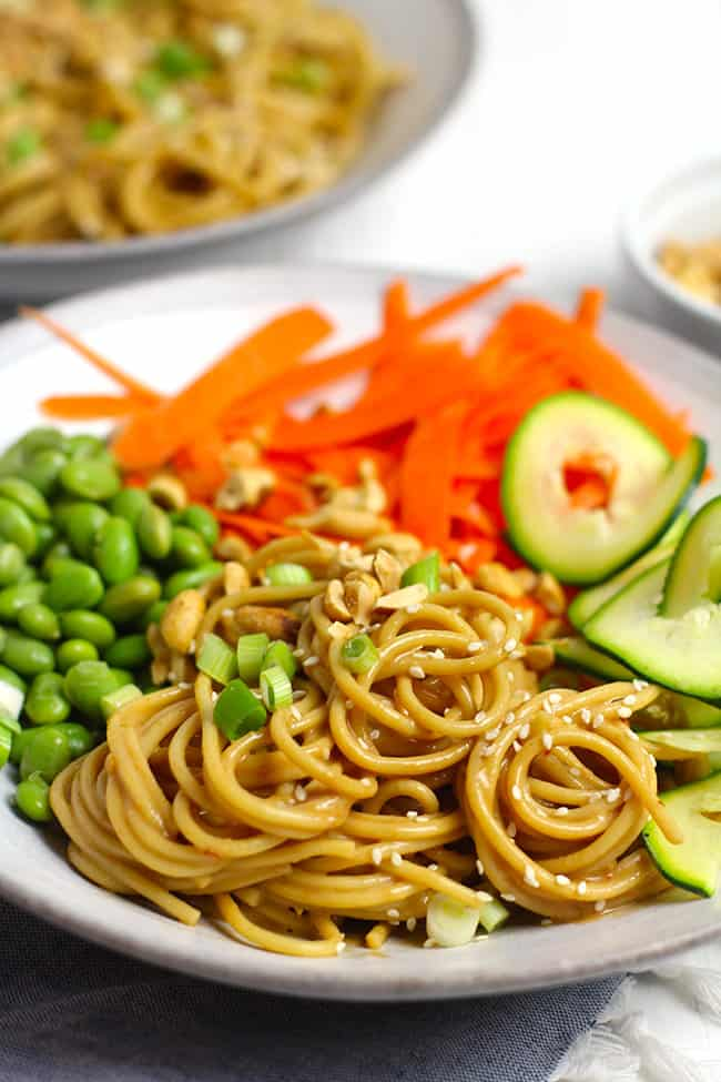 Side shot of a bowl of peanut sesame noodles, with vegetables.