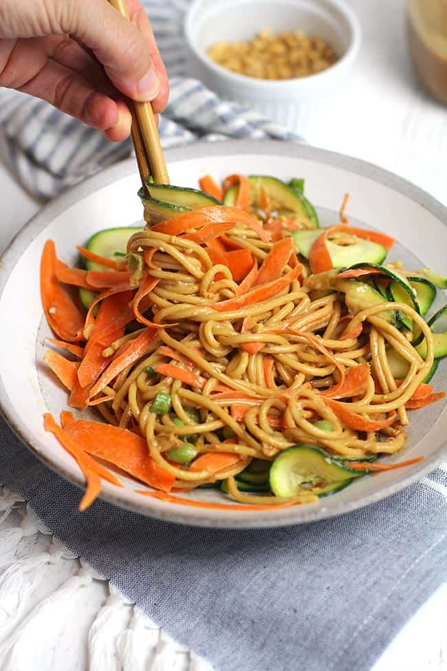 Side shot of a white bowl of peanut sesame noodles with vegetables, being twirled with some chopsticks.