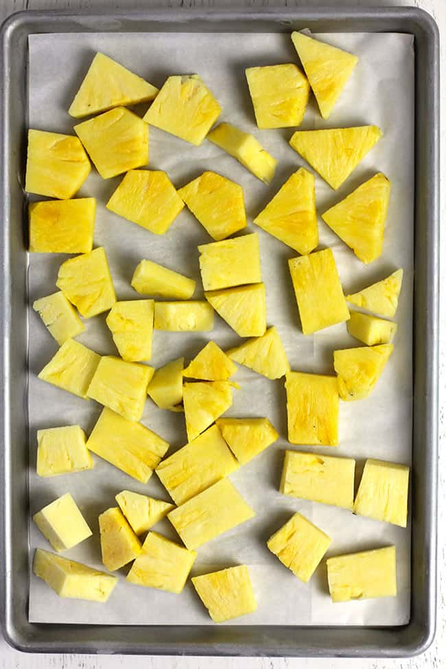 Overhead shot of a baking sheet full of pineapple chunks, ready for the freezer.