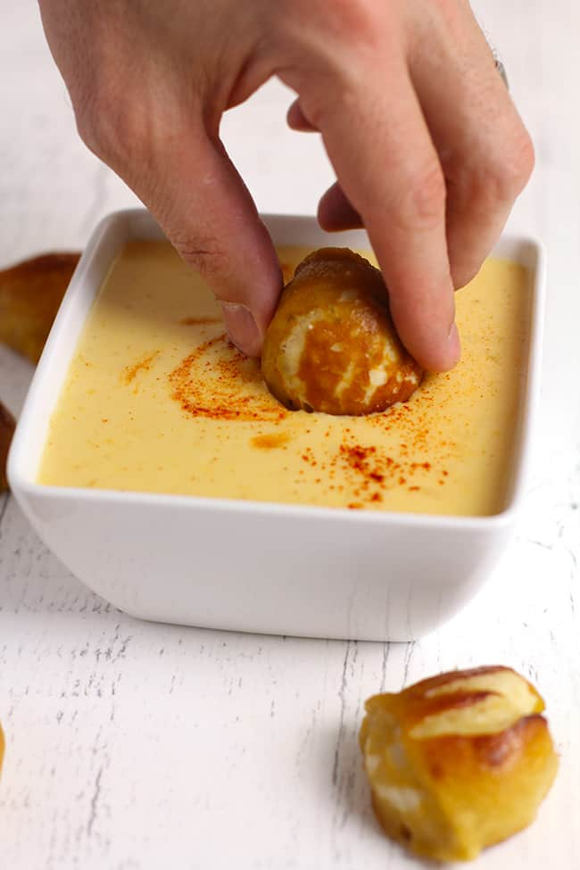Side shot of a hand dipping a pretzel bite into a square white bowl of spicy beer cheese dip, on a white background.