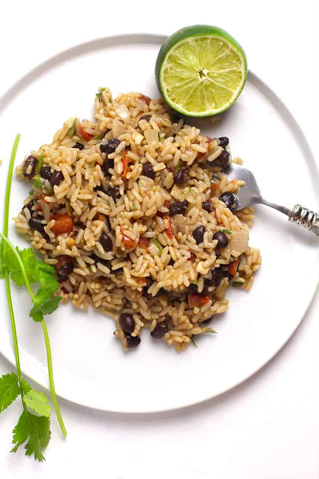 A white plate with a serving of Spanish Rice and beans and a fork.