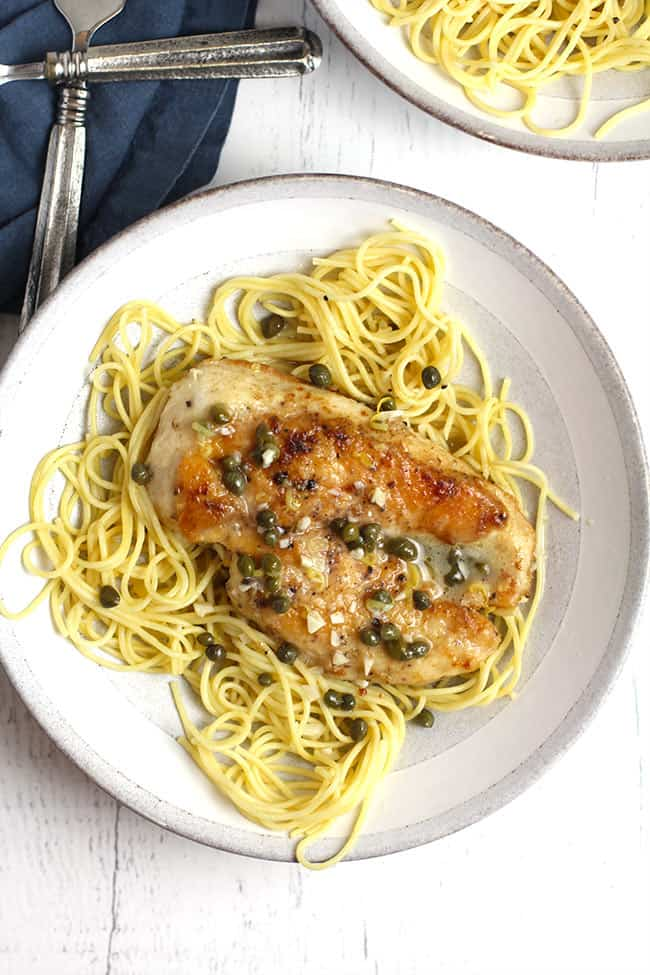 Overhead shot of two bowls of chicken piccata over pasta noodles, on a white background with a blue napkin.