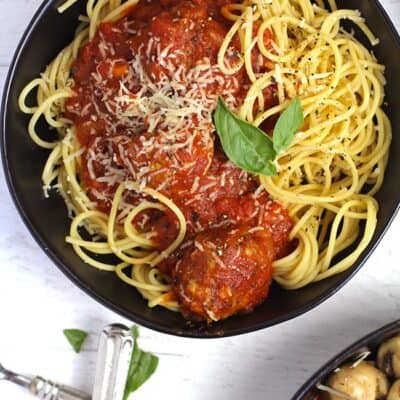 Overhead shot of a black bowl of homemade spaghetti and meatballs, on a white background.