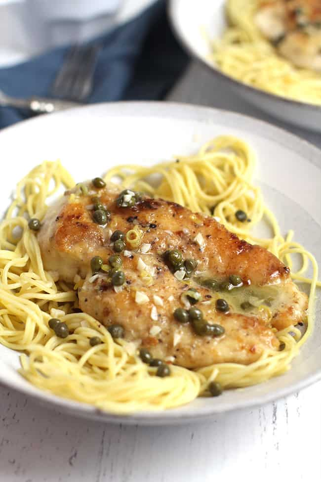 Side shot of a bowl of chicken piccata over pasta, with a lemon caper sauce.