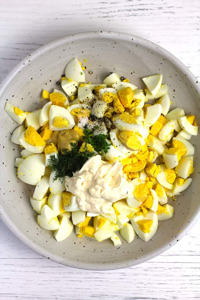 A bowl of the egg salad ingredients, before mixing.