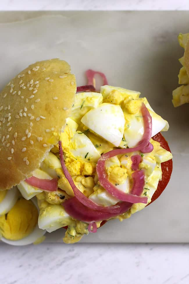 Overhead shot of an egg salad sandwich with the top bun off, with pickled onions and tomatoes.
