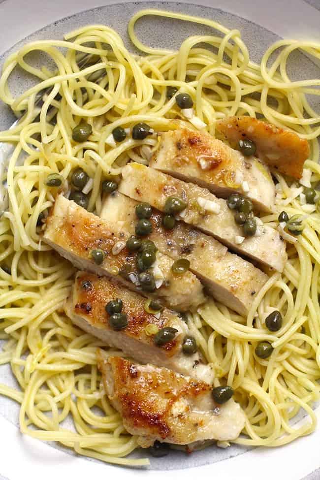 Closeup shot of some sliced chicken piccata over pasta, with a lemon caper sauce.