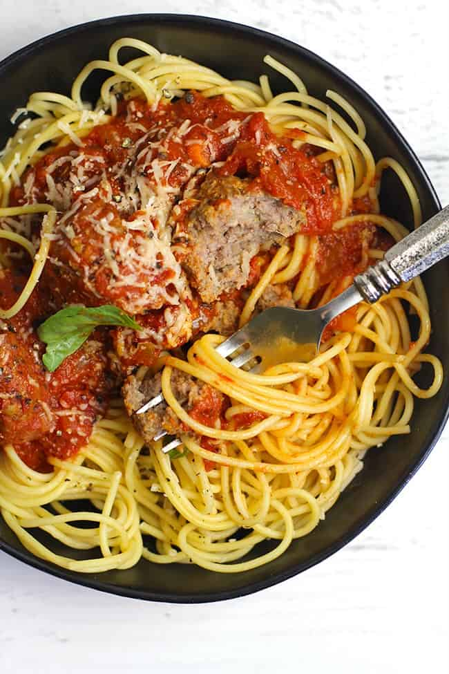 Closeup of a black bowl of homemade spaghetti and meatballs, with a fork twirling noodles.
