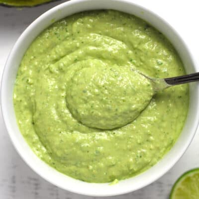 A bowl of creamy avocado dressing, with a spoon inside.