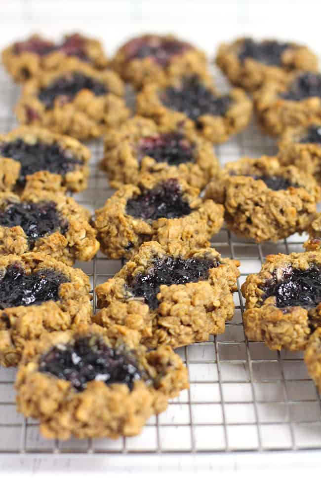 Side shot of some oatmeal breakfast cookies, with jelly in the middle, on a wire rack.
