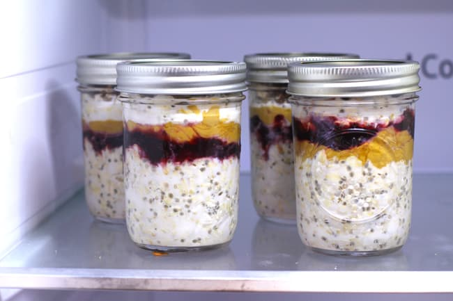 Side shot of four jars of overnight oats in a refrigerator.