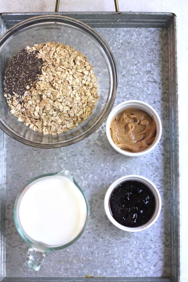 Overhead shot of overnight oats ingredients, including oatmeal, chia seeds, milk, peanut butter, and jelly.