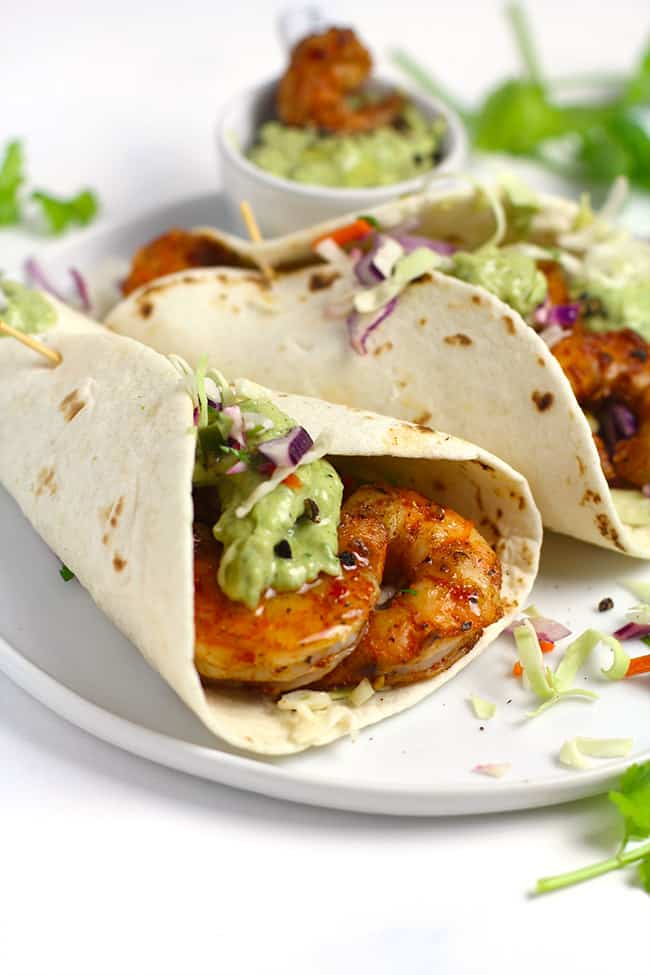 Side shot of two grilled shrimp tacos, with creamy avocado dressing.