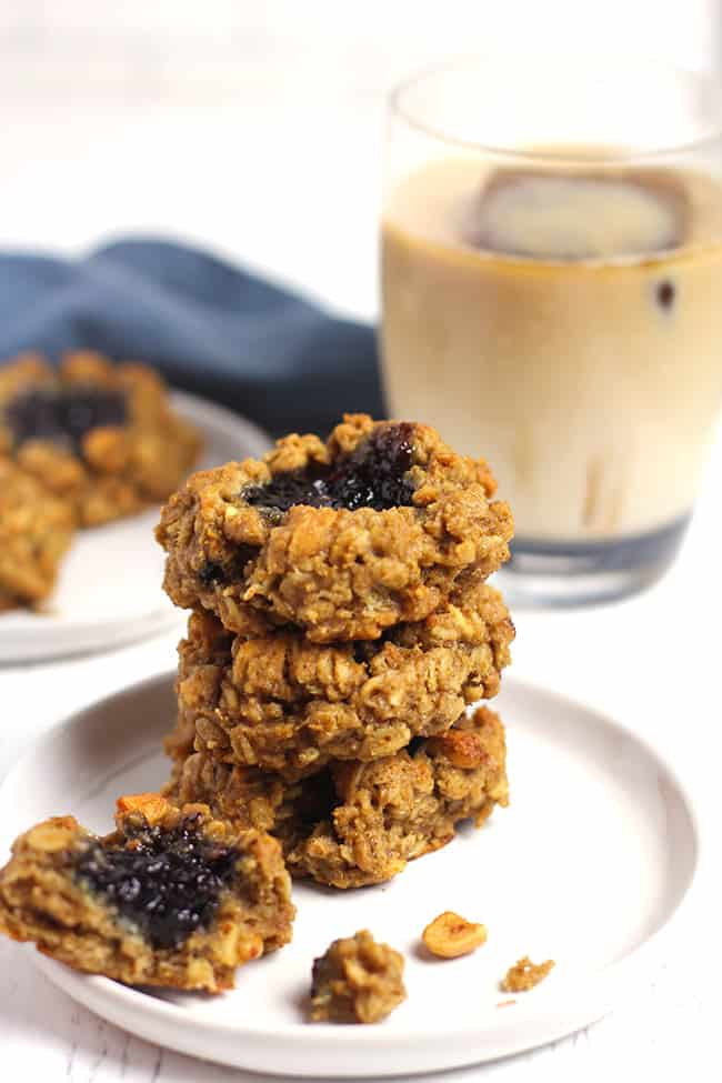 Side shot of a stack of three healthy oatmeal breakfast cookies on a white plate, with a cup of cold brew in the background.