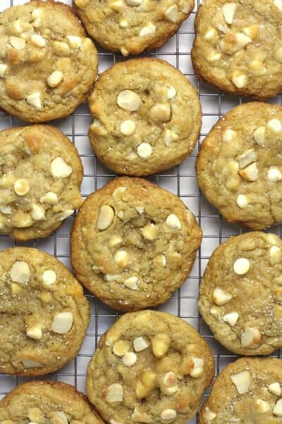 A bunch of white chocolate macadamia nut cookies on a cooling rack.
