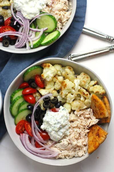 Overhead shot of two Greek Chicken Bowls with Chicken, on a white background.