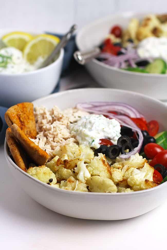 Side shot of two Greek Cauliflower Bowls with Chicken.