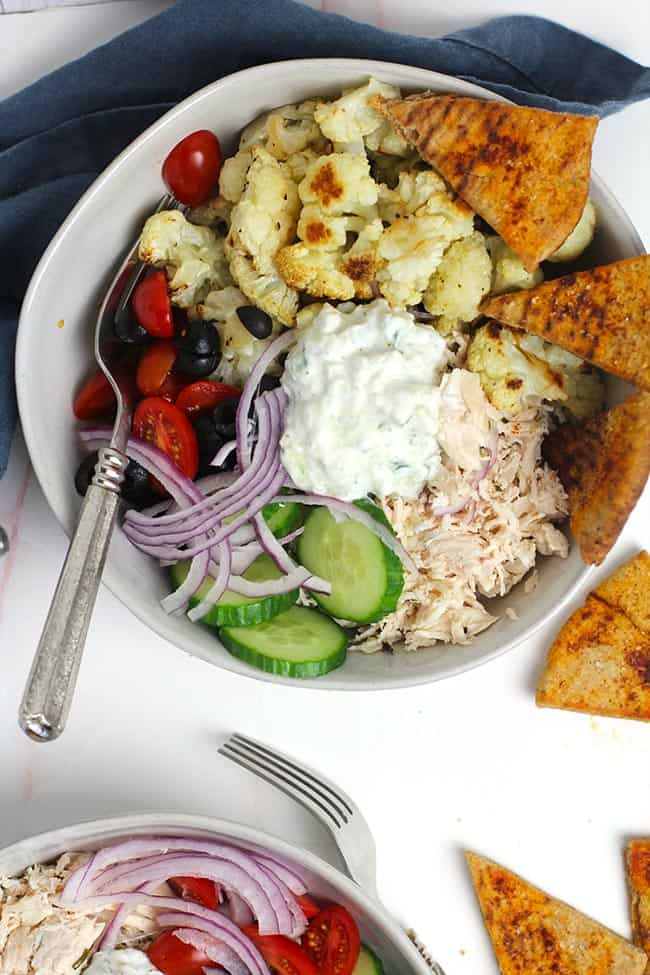 Close up of a Greek Cauliflower Bowl with Chicken, with some baked pita chips.