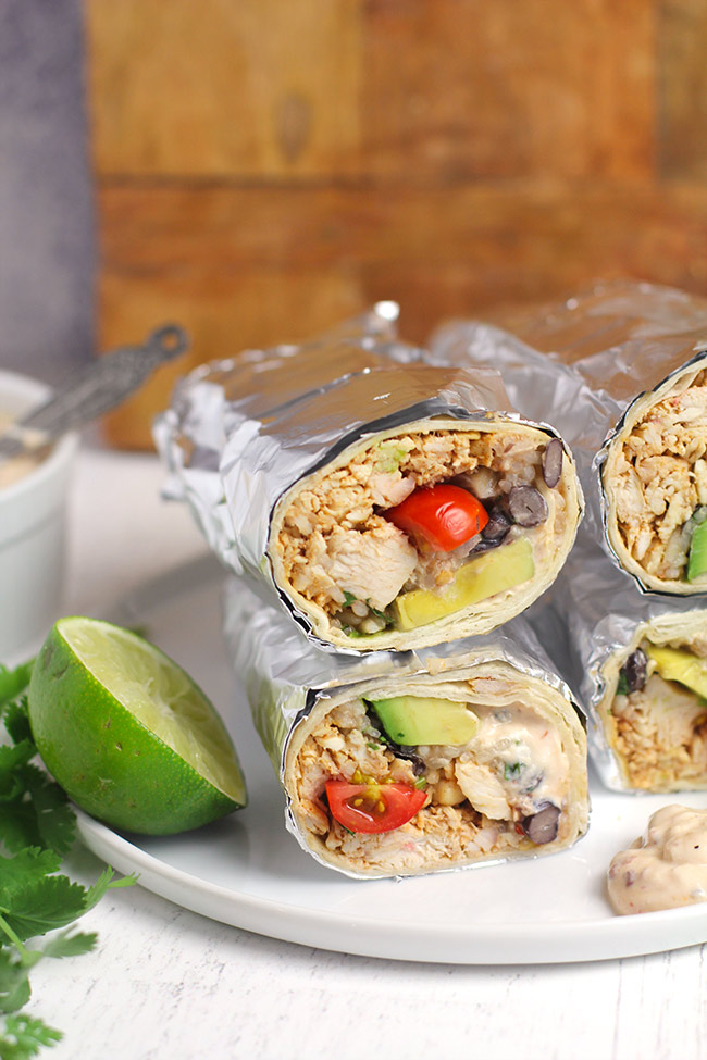 Side view of Mexican Chicken Burritos, wrapped in foil, on a white plate.