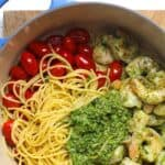 A pot of shrimp pesto pasta separated by ingredient.