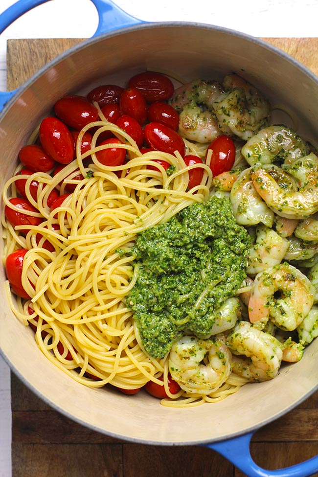 A stock pot of shrimp pesto pasta, divided by ingredient.